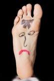 在妇女的脚的被绘的哀伤的面孔 免版税库存图片