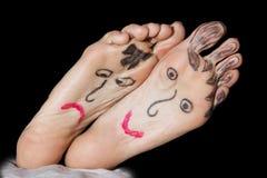 在妇女的脚的被绘的面孔 免版税库存图片