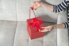 在妇女的豪华情人节礼物移交沙发 节日礼物的概念 免版税库存照片