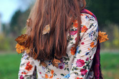 在妇女的头发的秋叶 免版税库存照片