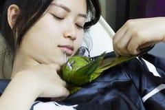 在妇女的绿色金刚鹦鹉鸟宠物戏剧 免版税库存照片
