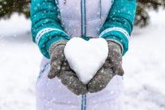 在妇女的heand的雪心脏 冬天浪漫概念 免版税库存照片