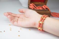 在妇女腕子的珊瑚串珠的镯子 库存照片