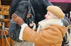 在妇女附近的黑色愉快的马 免版税图库摄影