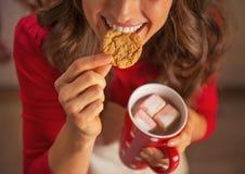 在妇女饮用的巧克力和吃圣诞节曲奇饼的特写镜头 免版税库存照片