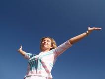 在妇女年轻人之下的蓝色愉快的天空 免版税库存照片