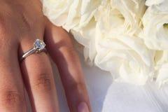 在妇女` s手上的一只典雅的订婚钻戒和白色Lisianthus花花束  库存图片