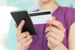 在妇女` s手上的选择聚焦拿着现代黑手机和塑料卡片,做在网上购物或检查她的银行帐户我 库存照片