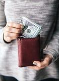 在妇女` s手是有一团的棕色皮革钱包一百美元 企业提议 美好的修指甲 图库摄影