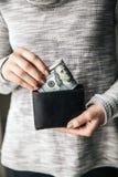 在妇女` s手是有一团的皮革钱包一百美元 企业提议 美好的修指甲 库存照片