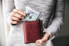 在妇女` s手是棕色皮革钱包 库存照片
