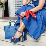 在妇女` s腿的美丽和时兴的鞋子 时髦的夫人辅助部件 蓝色鞋子、蓝色袋子、牛仔布礼服或者裙子 免版税库存照片