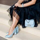 在妇女` s腿的美丽和时兴的鞋子 时髦的夫人辅助部件 蓝色鞋子、蓝色袋子、黑礼服或者裙子 免版税库存图片