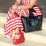 在妇女` s腿的美丽的时兴的鞋子 时髦的夫人辅助部件 红色鞋子、黑袋子、白色夏天礼服或者裙子 免版税库存照片