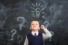 在委员会电灯泡有一个想法画的男孩 图库摄影