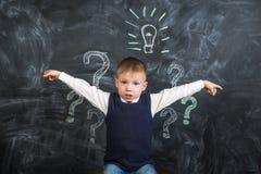 在委员会电灯泡有一个想法画的男孩 免版税库存照片