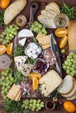 在委员会的不同的开胃菜:乳酪,熏火腿,火腿,面包,橄榄,葡萄 库存照片
