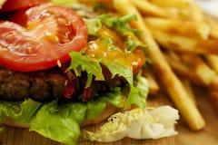 在委员会的乳酪汉堡用炸薯条 免版税库存图片