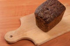 在委员会的切的黑麦面包 木的表 顶视图 库存照片