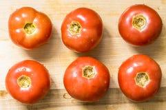 在委员会的新鲜的湿蕃茄背景的 免版税库存照片