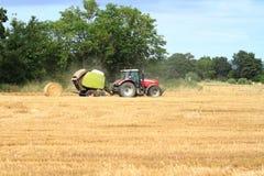 在委托干草的麦地的红色拖拉机 免版税库存照片