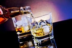 在威士忌酒玻璃前面的男服务员倾吐的威士忌酒在轻的色彩蓝色迪斯科 库存图片