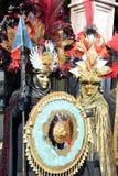 在威尼斯加州期间,男人和妇女一对未认出的夫妇穿戴与金面具,红色和黑羽毛帽子的精心制作的华丽服装 图库摄影