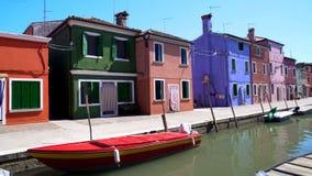 在威尼斯式运河停放的红色汽艇,美丽的五颜六色的房子,Burano 库存图片