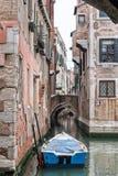 在威尼斯式运河横穿的偏僻的蓝色小船 库存照片