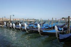 在威尼斯水中停放的长平底船 免版税库存图片