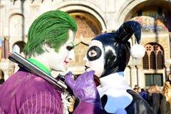 在威尼斯狂欢节期间,一对未认出的男人和妇女夫妇穿说笑话者华丽服装 免版税图库摄影