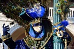 在威尼斯狂欢节期间,蓝色化装舞会服装的一个未认出的人与在后面的孔雀羽毛在左手保留一个面具 库存图片