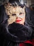 在威尼斯狂欢节期间,蝴蝶面具的可爱的妇女摆在 免版税图库摄影