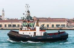 在威尼斯用力拖在旧港口前面的小船 免版税图库摄影