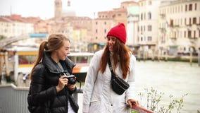 在威尼斯街道上的两年轻女人  他们中的一个拍周围的照片 影视素材