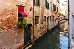 在威尼斯运河的典型的微小的桥梁 在窗口的花与威尼斯式快门 库存图片