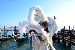在威尼斯Cernival期间,白色化装舞会服装的一名未认出的妇女与巨大的胆怯飞过 免版税库存照片
