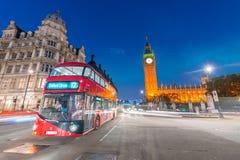 在威斯敏斯特桥梁在晚上,伦敦的红色公共汽车 免版税图库摄影
