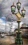 在威斯敏斯特桥梁的华丽街灯有2013年8月12日采取的伦敦眼的 库存图片