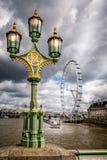 在威斯敏斯特桥梁的华丽街灯有2013年8月12日采取的伦敦眼的 免版税库存照片