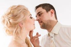 在婚姻的服装的美好的新婚佳偶夫妇亲吻 免版税库存照片