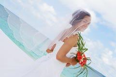 在婚礼之日的愉快的微笑的新娘在热带的海滩 库存图片