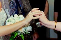 在婚礼他们戴着在新娘` s手上的一个圆环 图库摄影