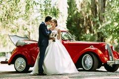 在婚礼和一辆汽车的夫妇在背景 库存照片