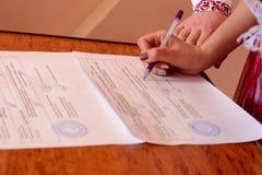 在婚礼期间的年轻美好的夫妇投入署名 库存照片
