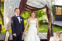 在婚礼期间的夫妇在曲拱下 库存图片