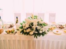 在婚礼桌安置的巨大的白色花束用食物 免版税图库摄影