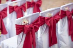 在婚礼椅子的大红色弓 免版税库存照片