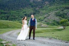在婚礼的夫妇盛装与花花束,并且绿叶在手里反对领域的背景在 库存图片