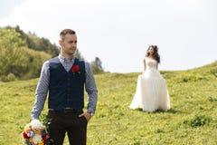 在婚礼的夫妇盛装与花花束,并且绿叶在手里反对领域的背景在 免版税库存照片